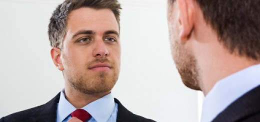 Portrait of a businessman looking at himself in the mirror